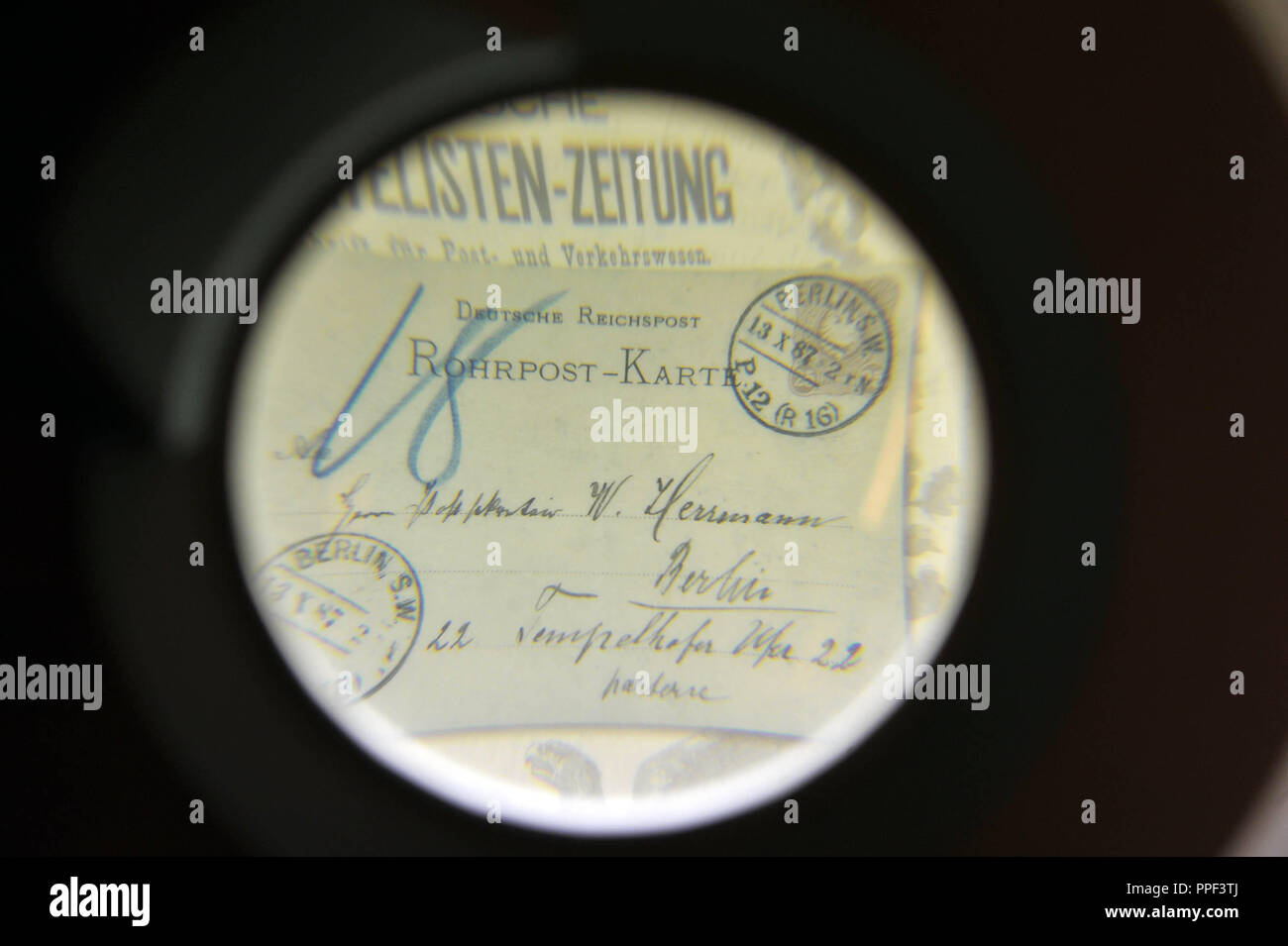Old stamp under a magnifying glass in the Library of Philately and Postal History on the 3rd floor of the Munich City Library in Gasteig. - Stock Image