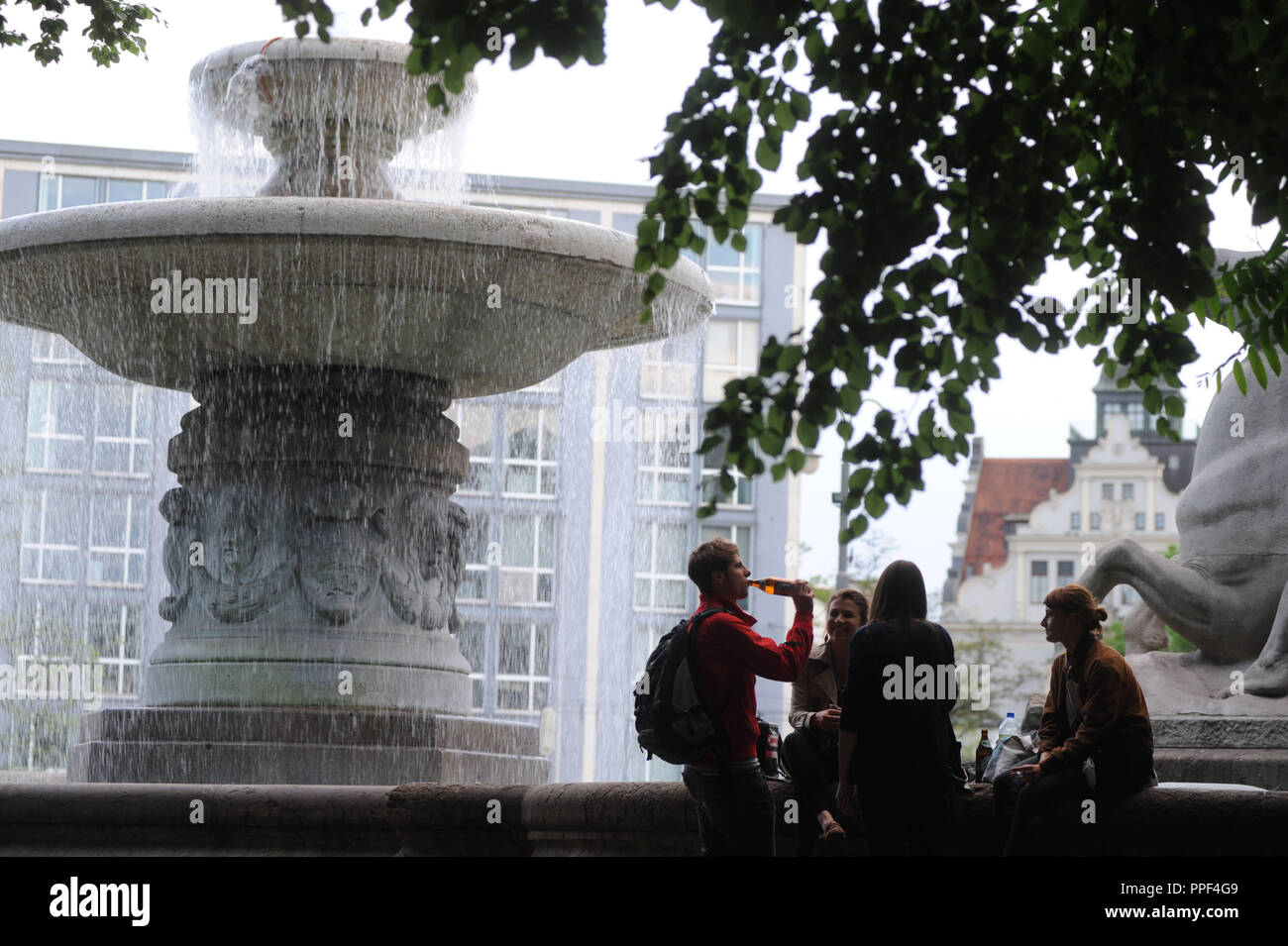 Young people on a cool spring evening at the fountain on Lenbachplatz. - Stock Image