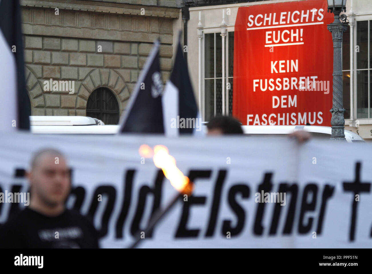 """The State Opera and the Residenz Theater protest against a neo-Nazi march. The right-wing extremists commemorate the anniversary of the death of one of their comrades, Reinhold Elstner, who set himself on fire in 1995 to protest against the Wehrmacht exhibition. Above the entrance of the opera there is a giant red cloth with the words """"Get lost! No inch of fascism"""". Stock Photo"""