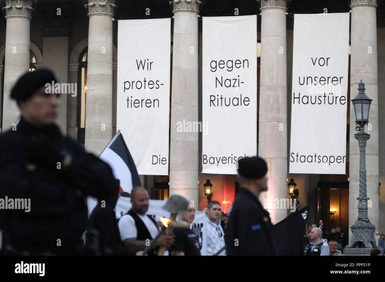 "The State Opera and the Residenz Theater protest against a neo-Nazi march. The right-wing extremists commemorate the anniversary of the death of one of their comrades, Reinhold Elstner, who set himself on fire in 1995 to protest against the Wehrmacht exhibition. Above the entrance of the opera there are long white cloths bearing the inscription ""We protest against Nazi rituals at our doorstep - the Bavarian State Opera."" Stock Photo"