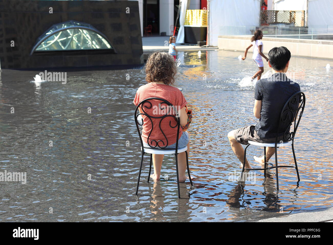 A couple of adults sitting in a city wading pool in downtown Montreal,Canada - Stock Image
