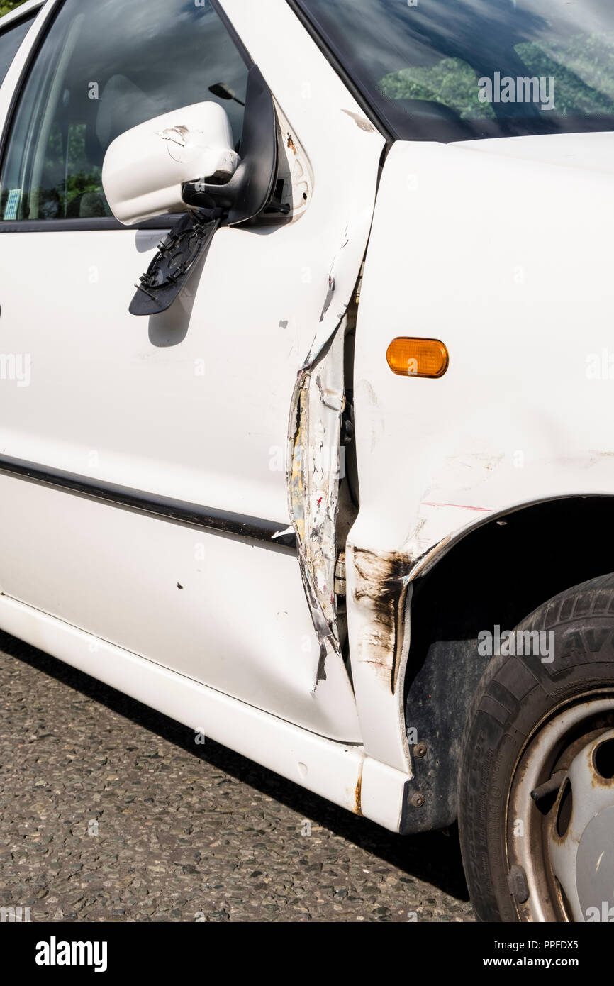 Car crash damage. Broken car door, damaged wing mirror and wing following a collision, Nottinghamshire, England, UK - Stock Image
