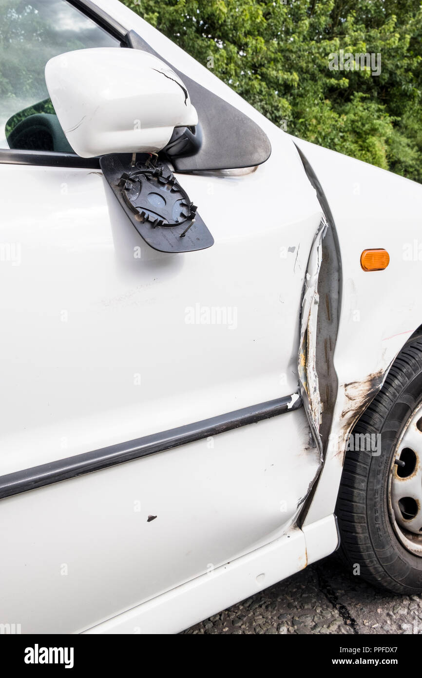 Car accident. Damage to a car door, wing mirror and wing following a collision, Nottinghamshire, England, UK - Stock Image