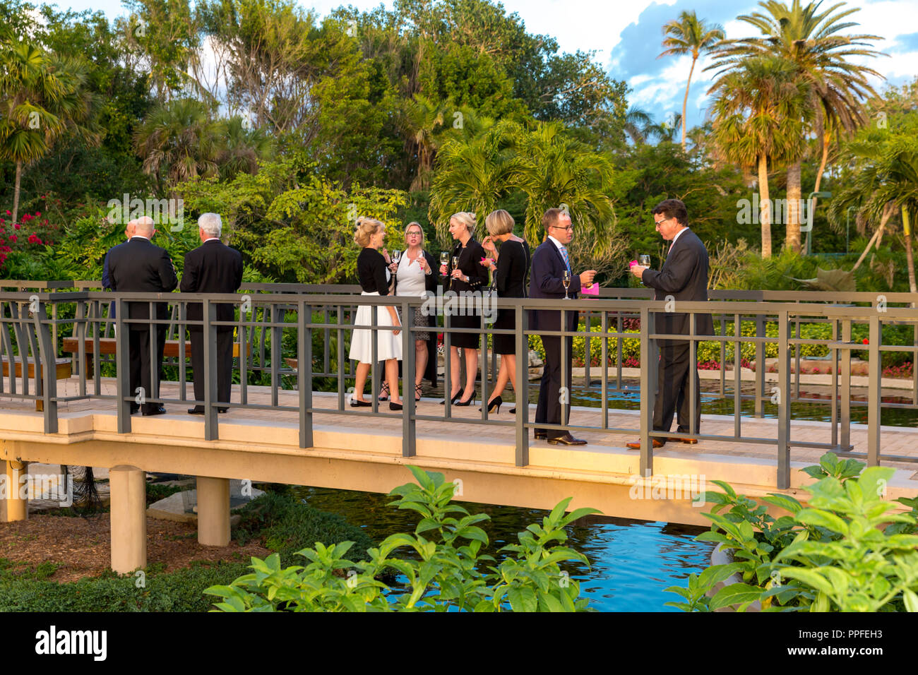 Guests in conversation at outdoor garden party, Naples, Florida, USA - Stock Image