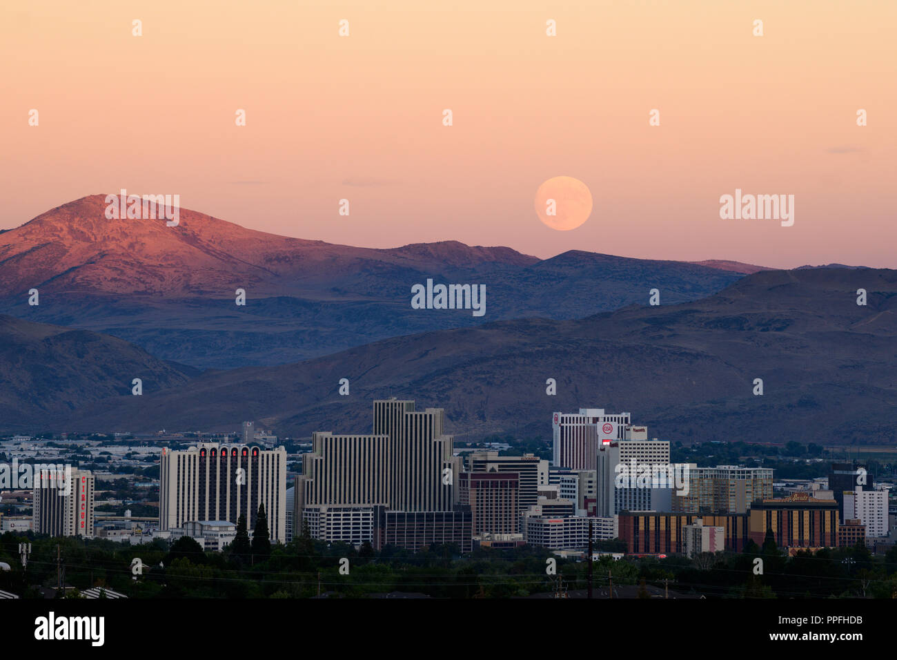 Full Harvest Moon rise over downtown Reno skyline just after the fall equinox, Reno, Nevada, USA. - Stock Image