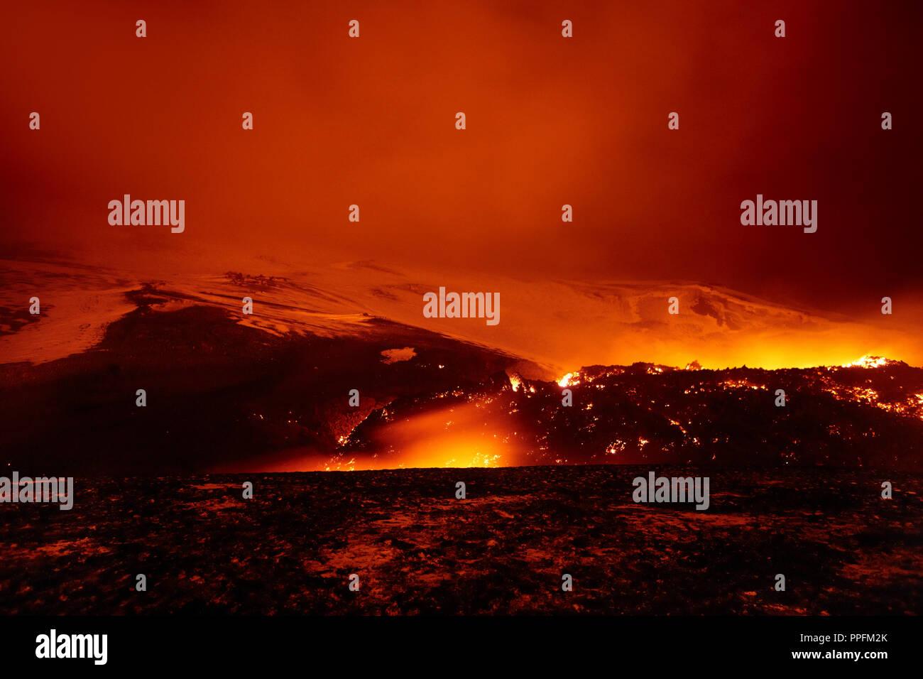 Glowing lava and lava flow at night on Fimmvörðuháls volcano, fissure eruption on Fimmvörduhals - Stock Image