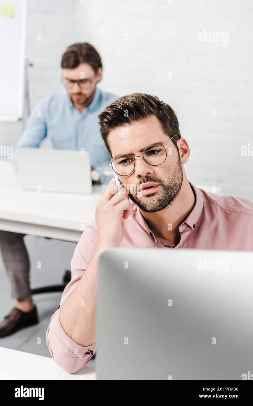 businessman working with computer and talking by phone at modern office with blurred colleague on background - Stock Image