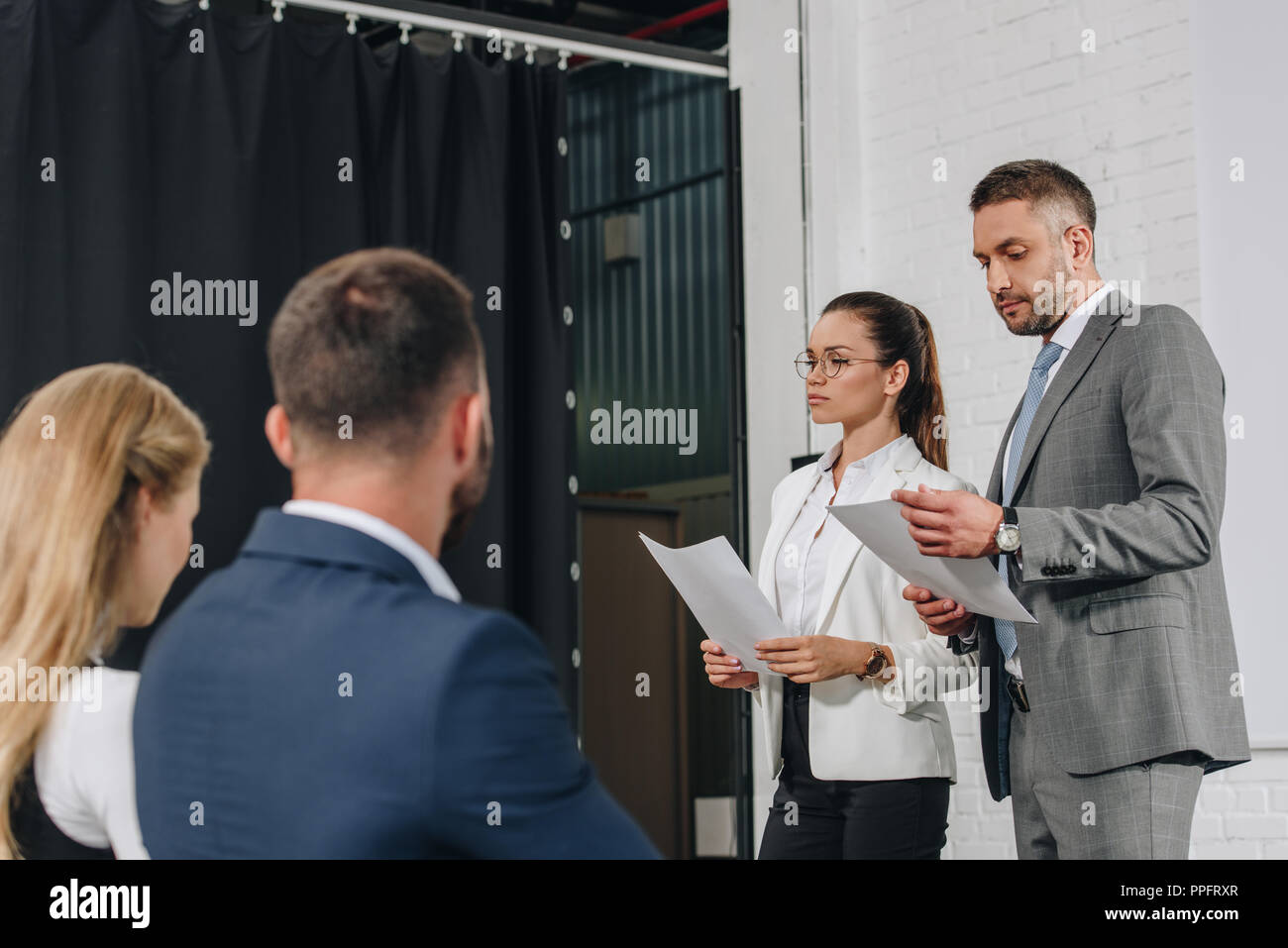 business trainers standing on stage with documents in hub - Stock Image
