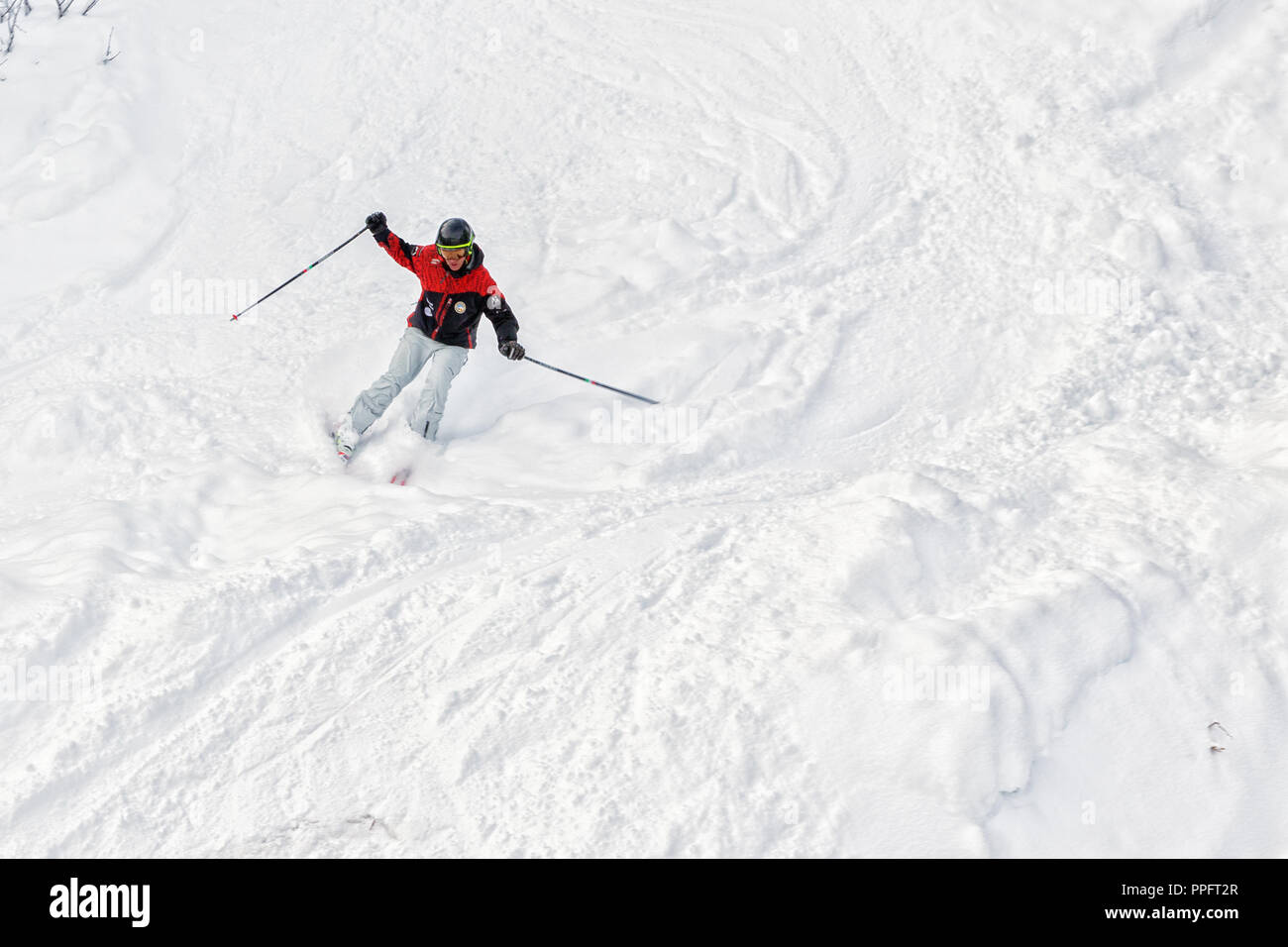PYRENEES, ANDORRA - FEBRUARY 6, 2018: Downhill skier moves down from a steep slope. It is a lot of friable snow, freeride - Stock Image