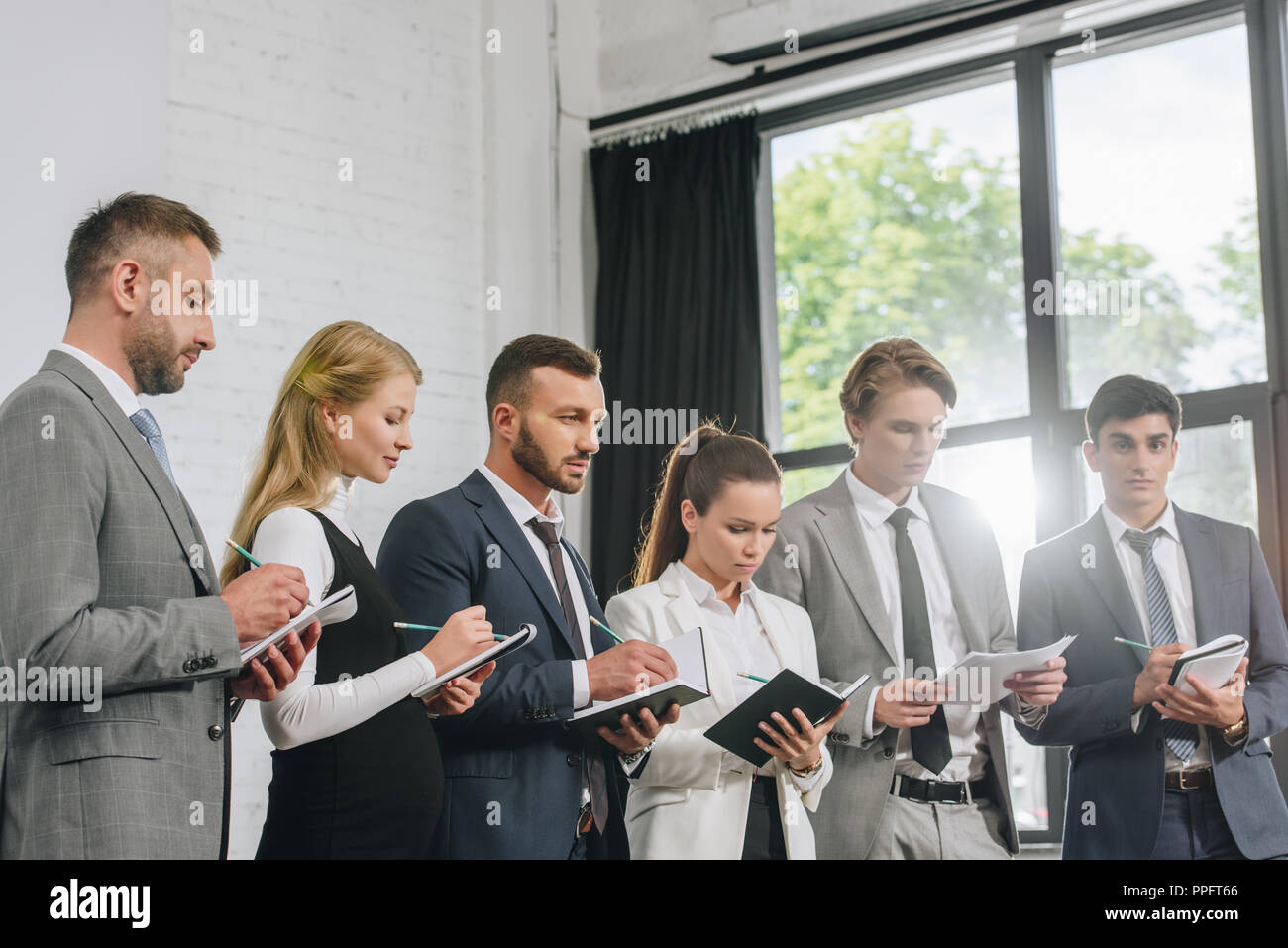 businesspeople standing in row and writing something to notebooks during training in hub - Stock Image