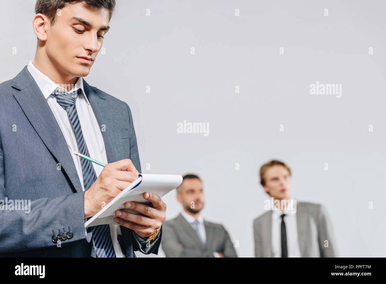 handsome businessman writing something to notebook with pencil in hub - Stock Image