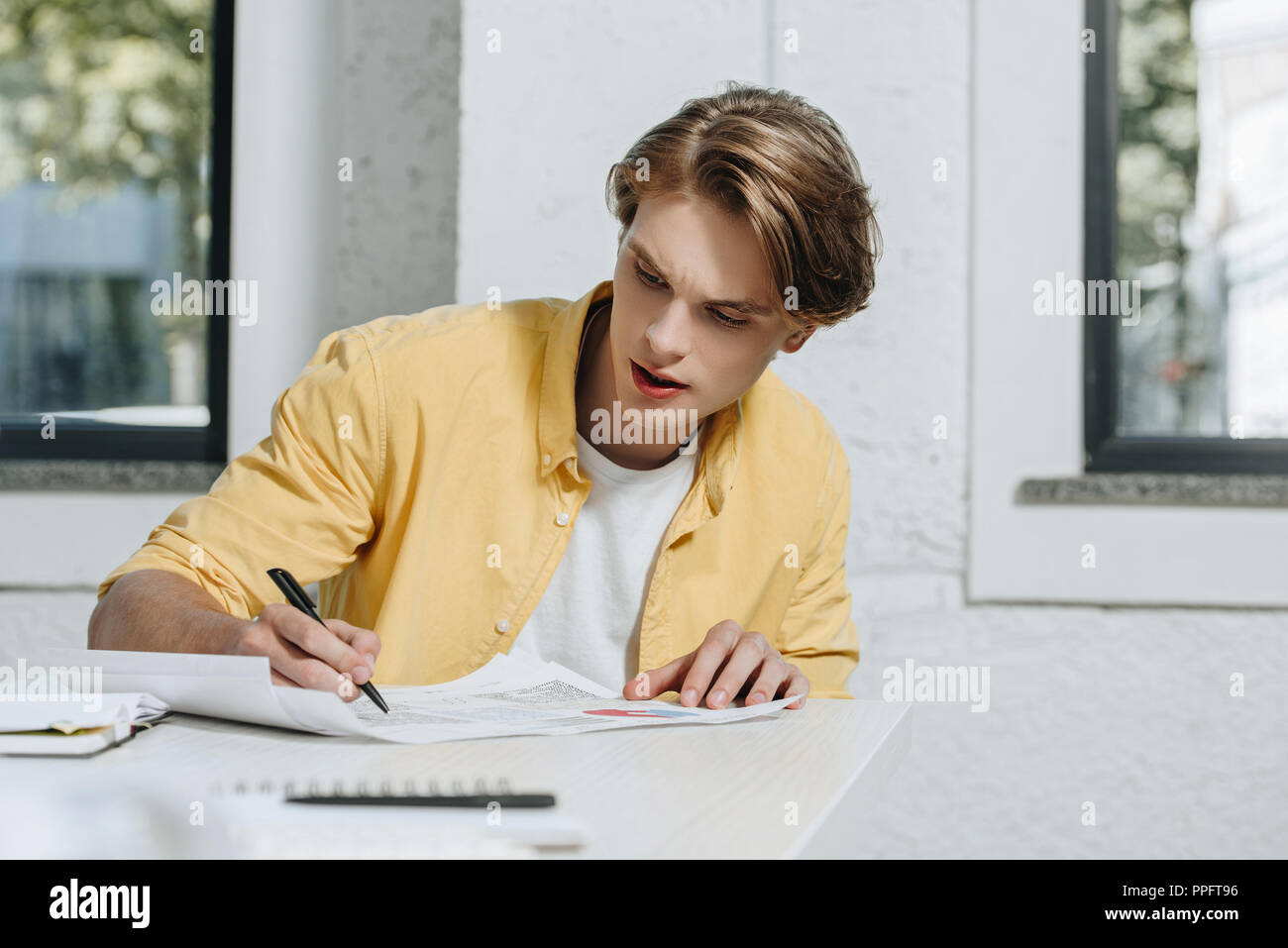handsome businessman writing something to documents in office - Stock Image