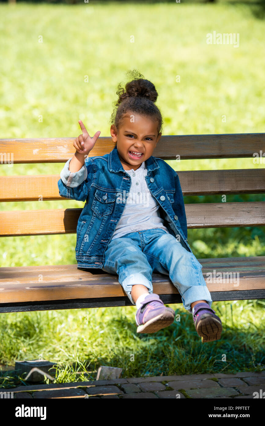 grimacing african american kid gesturing and sitting on wooden bench - Stock Image