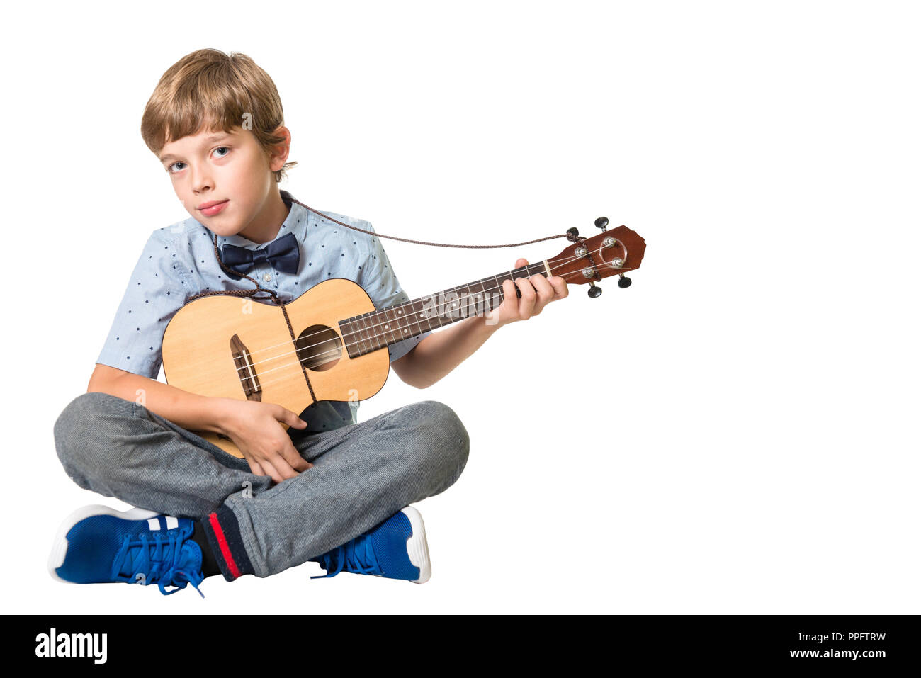 young adorable boy playing the ukulele, isolated on white background with space for text Stock Photo