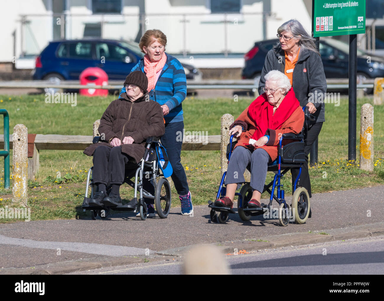People pushing elderly disabled people in wheelchairs in the UK. - Stock Image