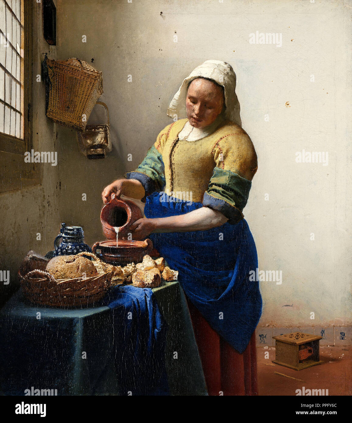 Johannes Vermeer - The Milkmaid. Circa 1660. Oil on canvas. Rijksmuseum Amsterdam, Netherlands. - Stock Image