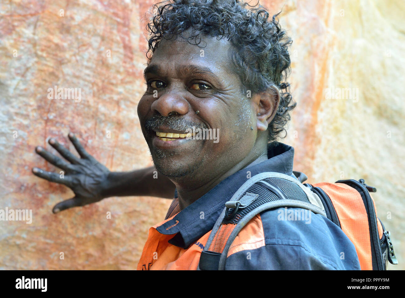 Aboriginal guide pointing out artwork in a rock art gallery on Injalak Hill, Arnhem Land, Northern Territory, Australia Stock Photo