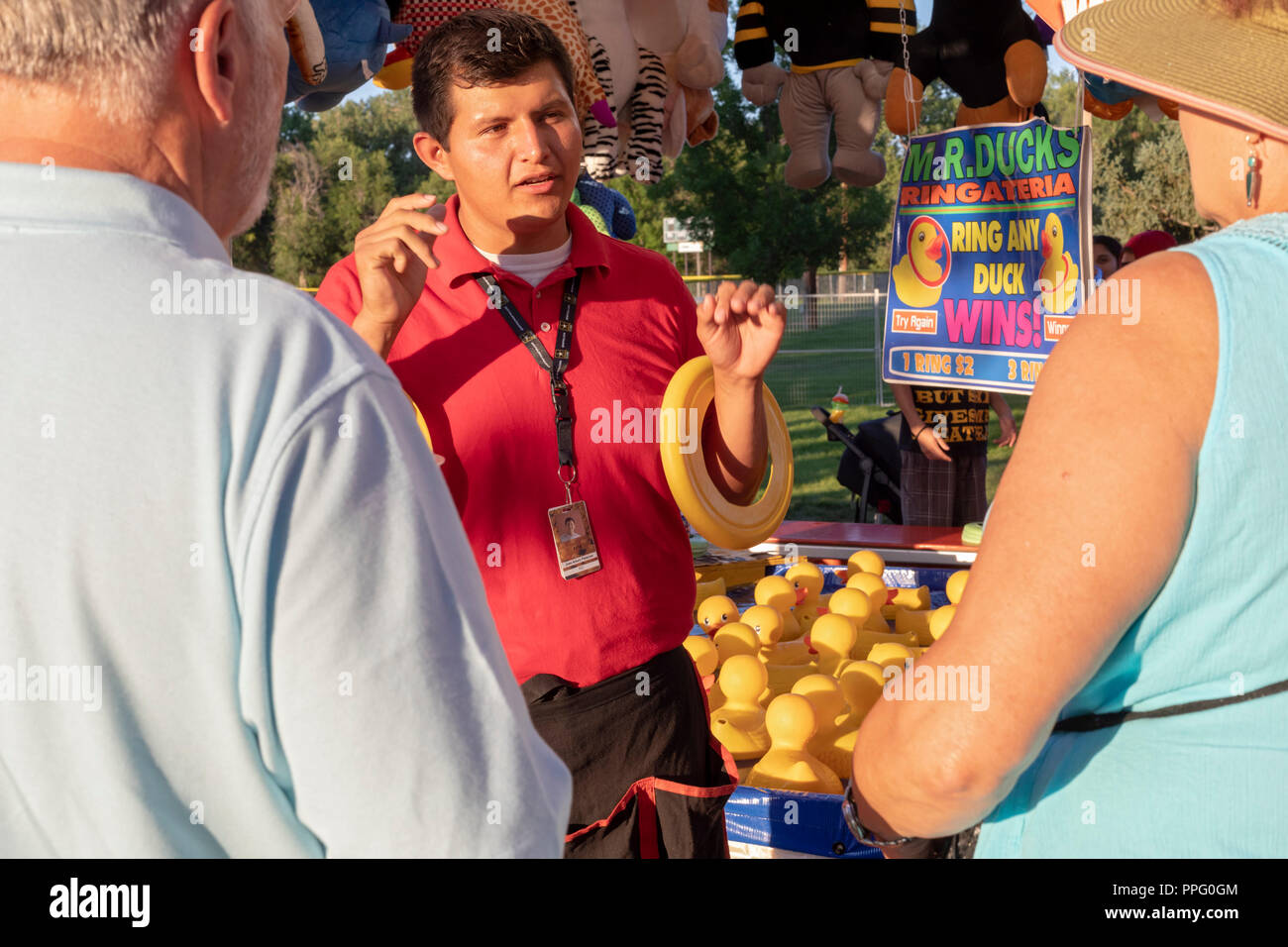 Wheat Ridge, Colorado - A worker explains a game at the annual Carnation Festival. The festival features food and entertainment. It was named for the  - Stock Image