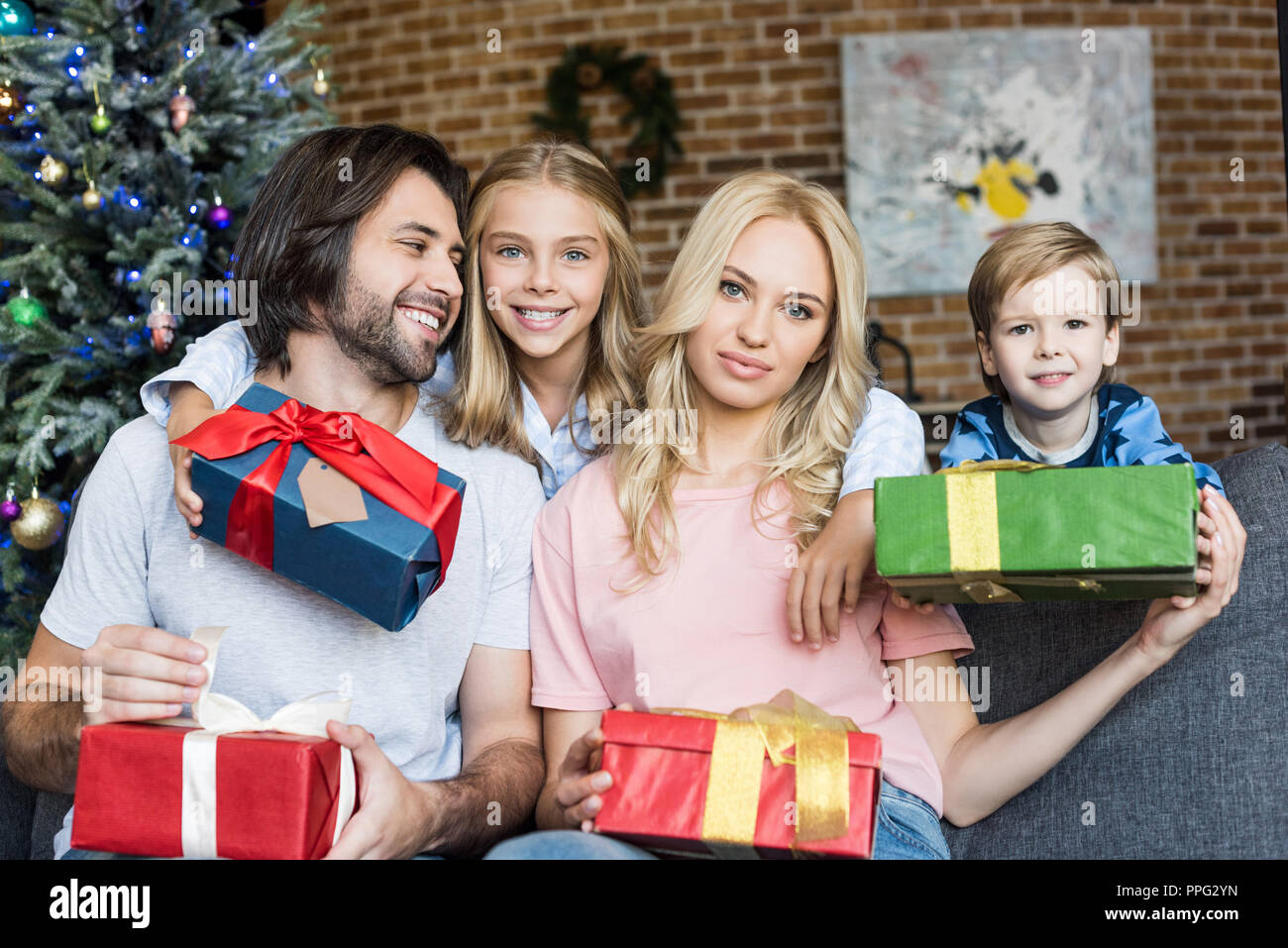 beautiful happy family with two children holding christmas gifts at ...