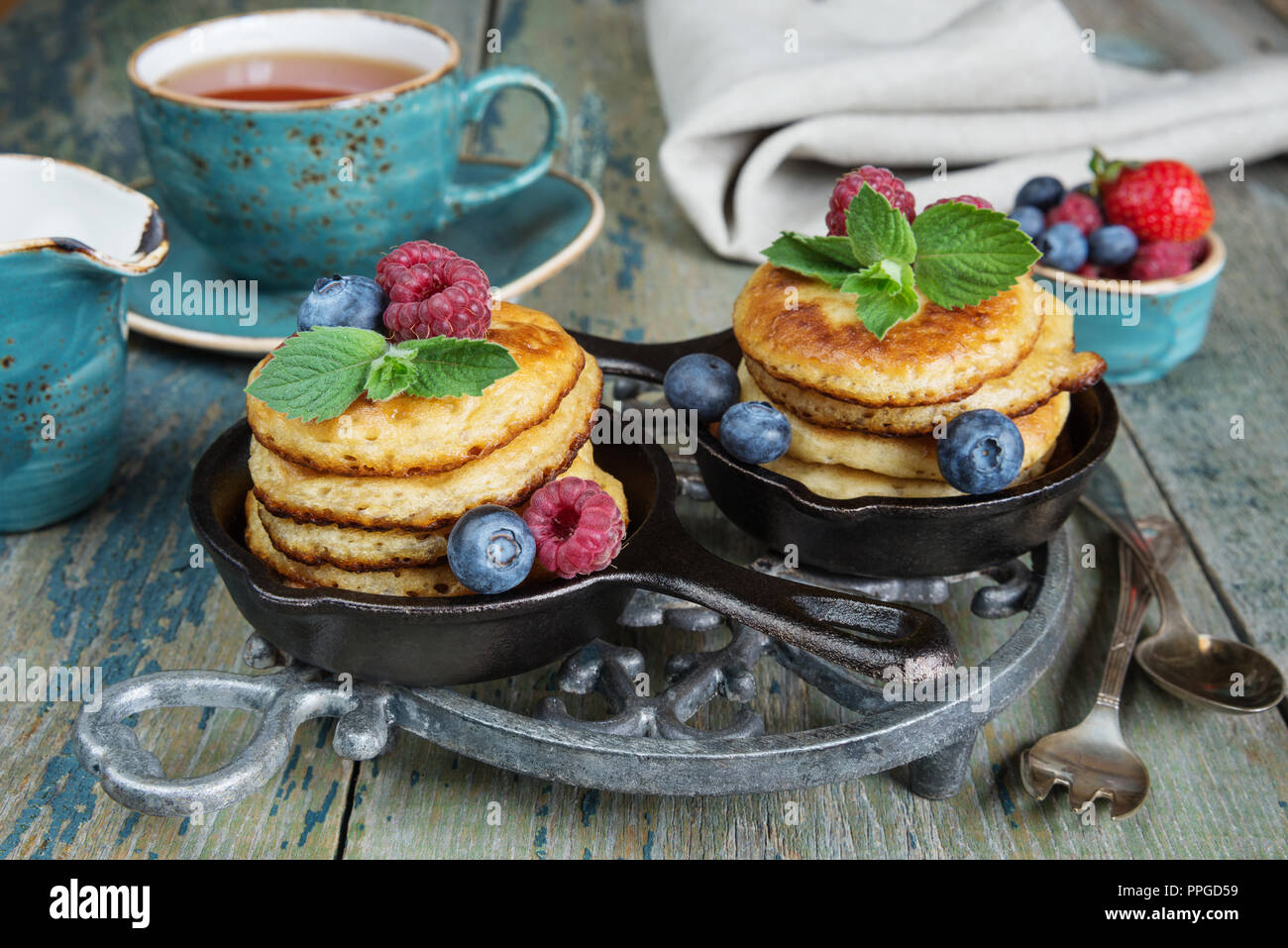 Breakfast of pancakes in cast-iron frying pans, fresh berries and black tea, in rustic style - Stock Image
