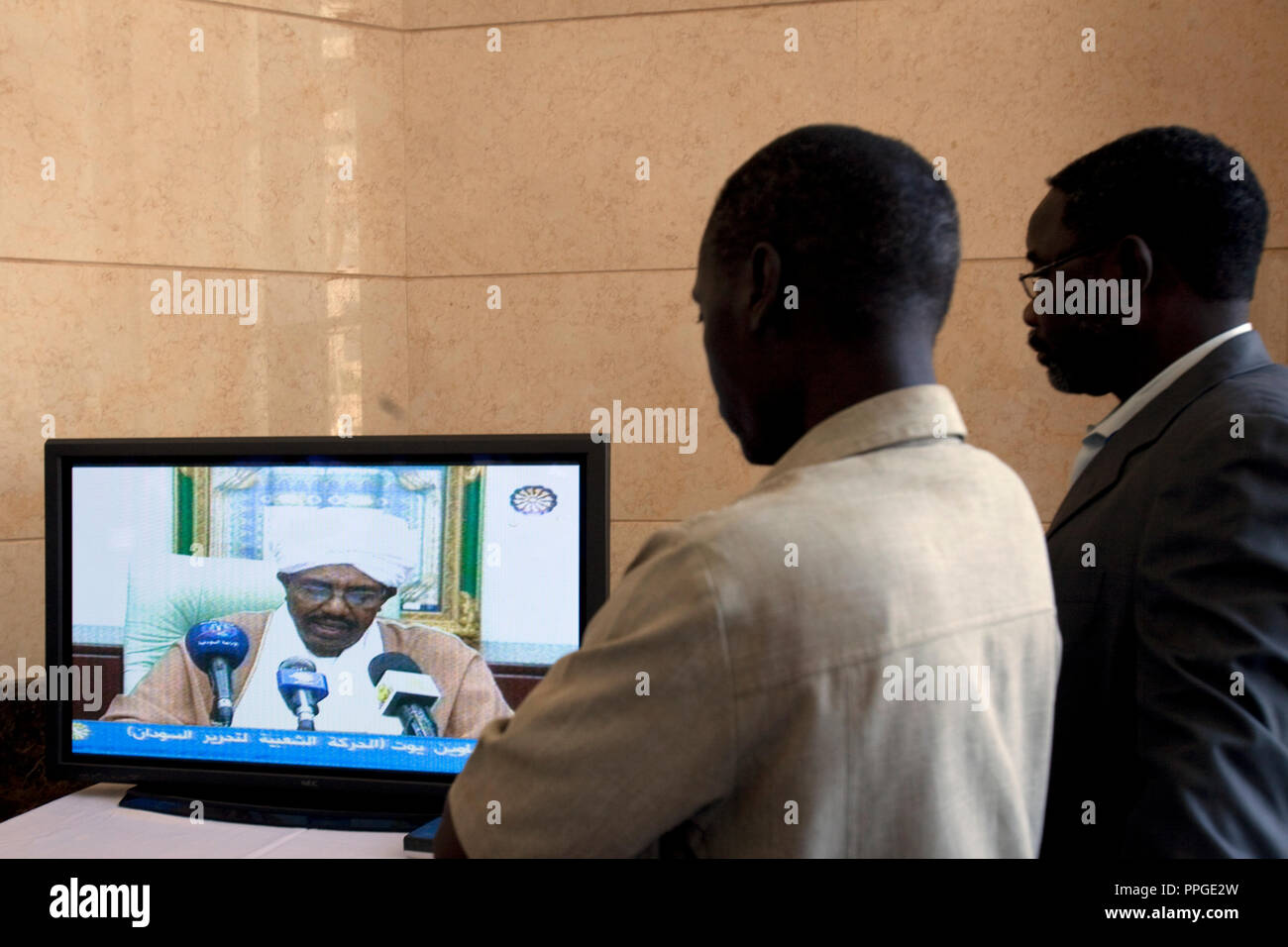 26 april 2010 - Friendship Hall Theatre, Karthoum, Sudan – Sudanese men follow a televised speech from Sudanese President Omar al-Bashir in Khartoum. Bashir appeared on state television soon after the result saying the Sudanese people 'have achieved this moral victory before the eyes of the world in a civilised, high class and shared manner'. Sudan's president Omar al-Bashir won another term in office Monday, according to election officials, with a comfortable majority (68 percent of the vote ) in elections marred by boycotts and fraud allegations, becoming the first leader to be elected while - Stock Image