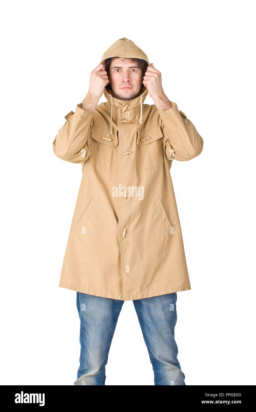 Young guy wearing in raincoat keeping his hood by hands - Stock Image