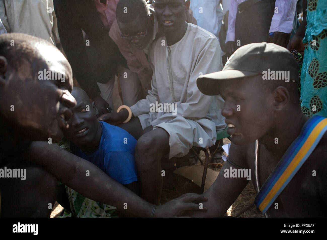 18 december 2010 - Juba, Southern Sudan - Members of the Dinka tribe from Bor, Jonglei State talk before the final of South Sudan's first commercial wrestling league between their tribe and the Mundari wrestlers from Central Equatoria State at Juba Stadium. The matches attracted large numbers of spectators who sang, played drums and danced in support of their favorite wrestlers. The match organizers hoped that the traditional sport would bring together South Sudan's many different tribes. Photo credit: Benedicte Desrus - Stock Image