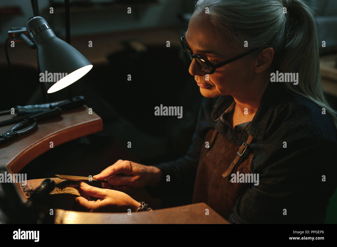 Goldsmith working and shaping an unfinished jewelry piece with a tool at a workbench in workshop. Mature female goldsmith working in her workshop. - Stock Image