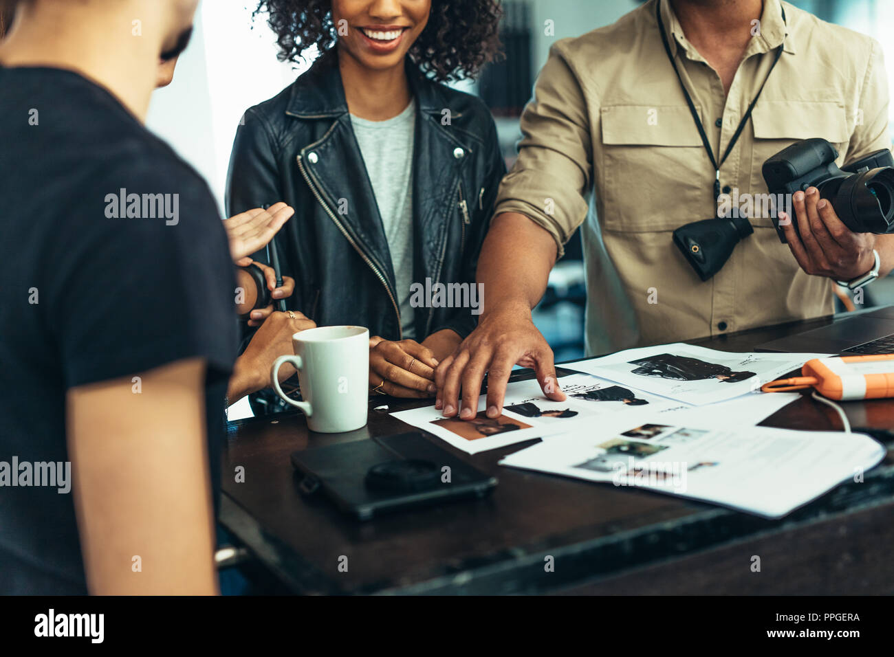 Photographer looking at photographs with model and his team. Photographer discussing about the photo shoot with his team. - Stock Image