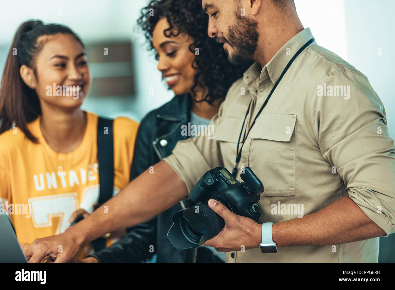 Photographer doing a review of the photo shoot with his team. Models looking at shoot photographs and smiling. - Stock Image