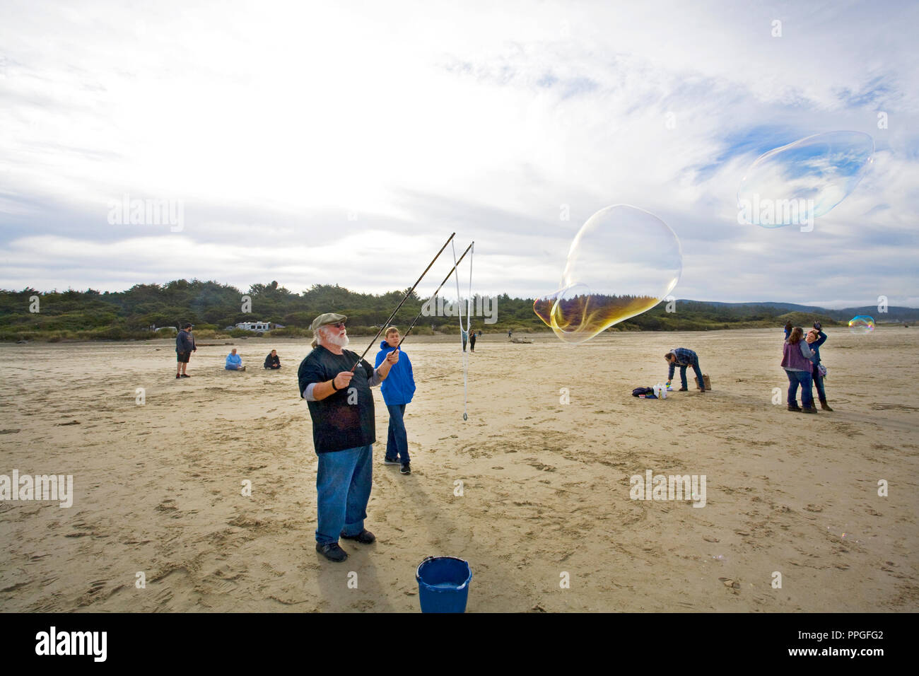 A man using a bubble wand to creat huge soap bubbles at a bubble blowing festival near yachats, Oregon - Stock Image