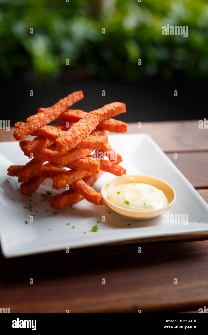 Food Photography / gastronomy close up shot of sweet potato fries with dipping sauce. - Stock Image