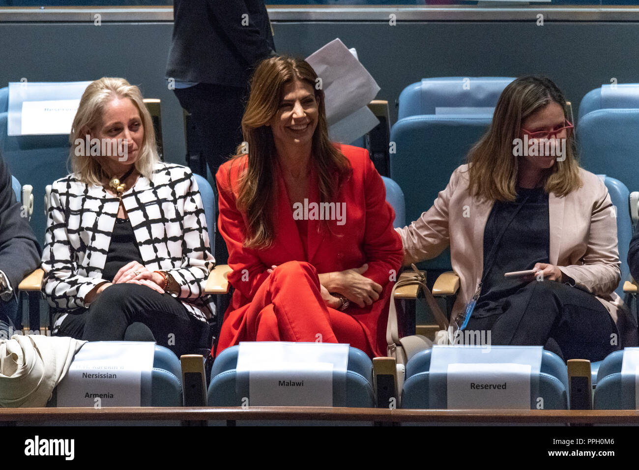 New York, USA, 24 September 2018.  Argentine First Lady Juliana Awada (wearing red) waits at a sidel seating while her husband Argentine President Mauricio Macri addresses the United Nations General Assembly.  Photo by Enrique Shore Credit: Enrique Shore/Alamy Live News Stock Photo