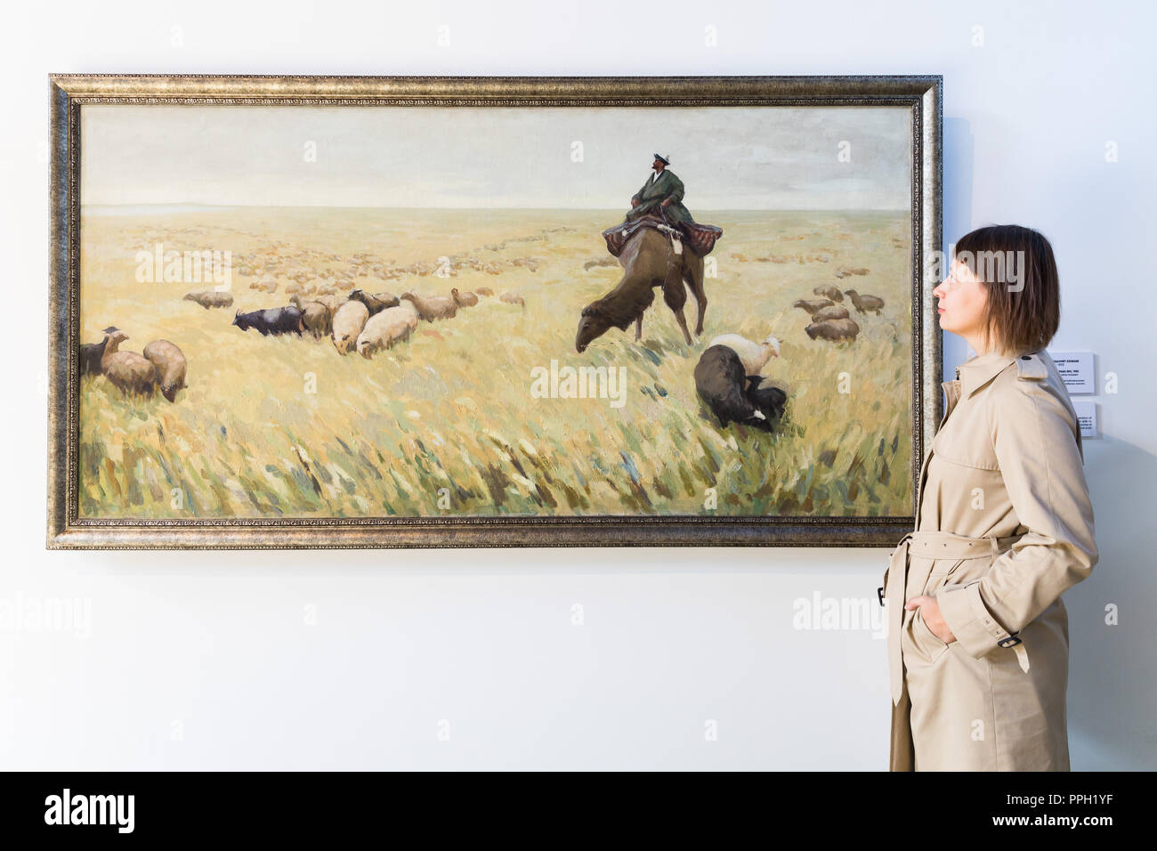London, UK. 25th September 2018. A visitor views The Song Of The Shepherd, 1982 by Moldakhmet Kenbayev. The Focus Kazakhstan: Post-Nomadic Mind exhibition features emerging and established artists and examines Kazakh contemporary art as a form of multi-channel discourse, drawing parallel dialogues between contemporary artists, their Soviet predecessors, and the newly termed subject matter of post-nomadism. The exhibition runs until 16th October 2018. Credit: Vickie Flores/Alamy Live News - Stock Image