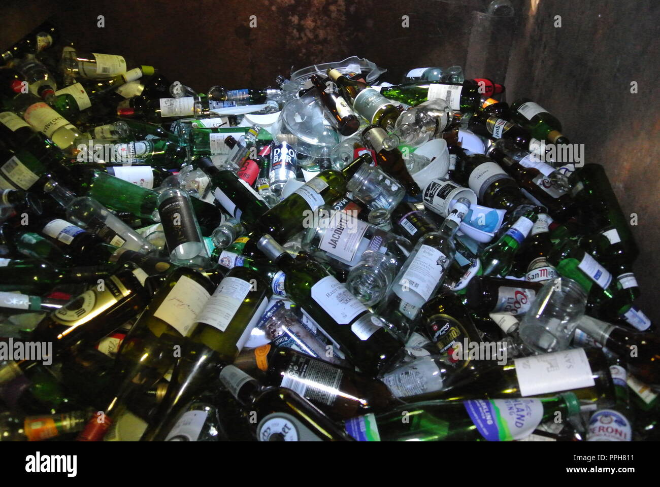 Glass bottles inside a bottle bank ready for recycling in England. - Stock Image
