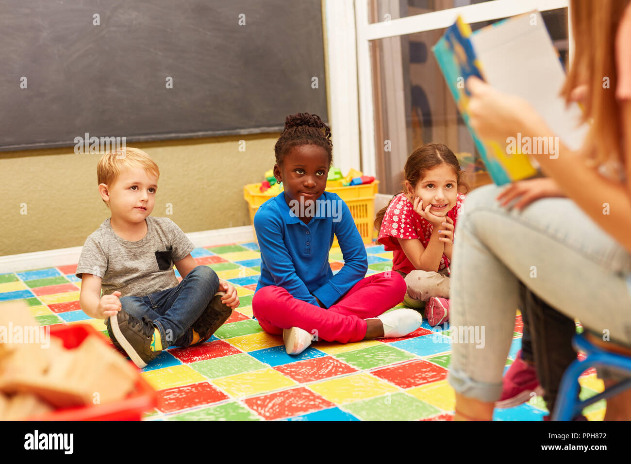 Group of children listen attentively while reading aloud from an exciting children's book - Stock Image