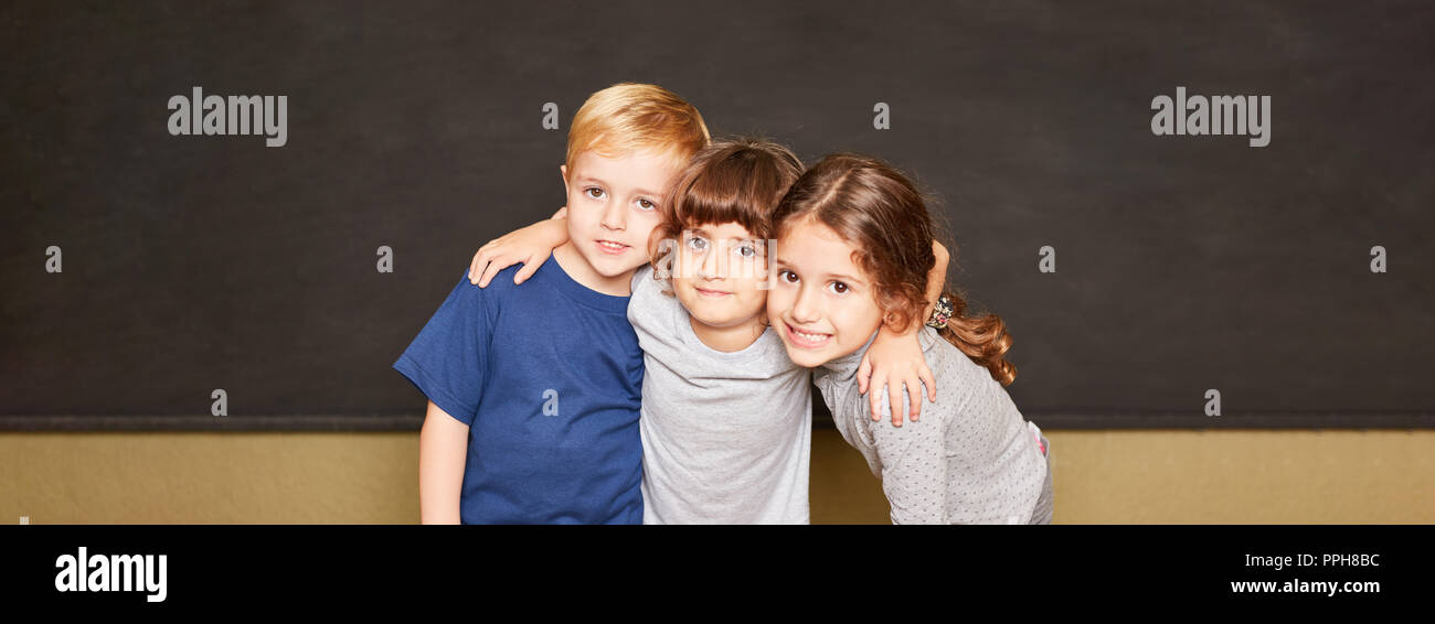 Group of kids is standing together in front of a blackboard in elementary school Stock Photo
