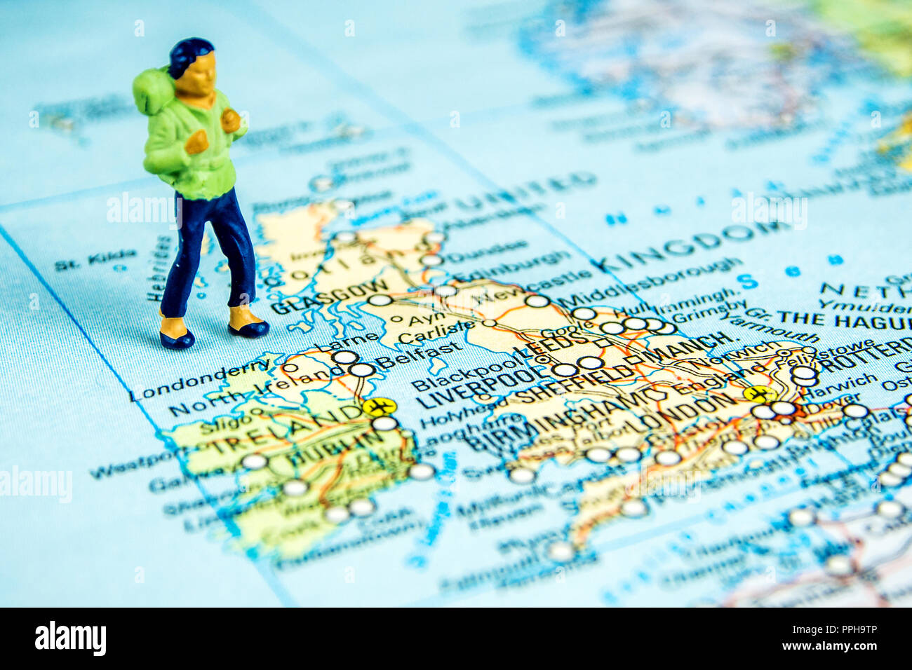 closeup of miniature figurine of young traveller standing on ...