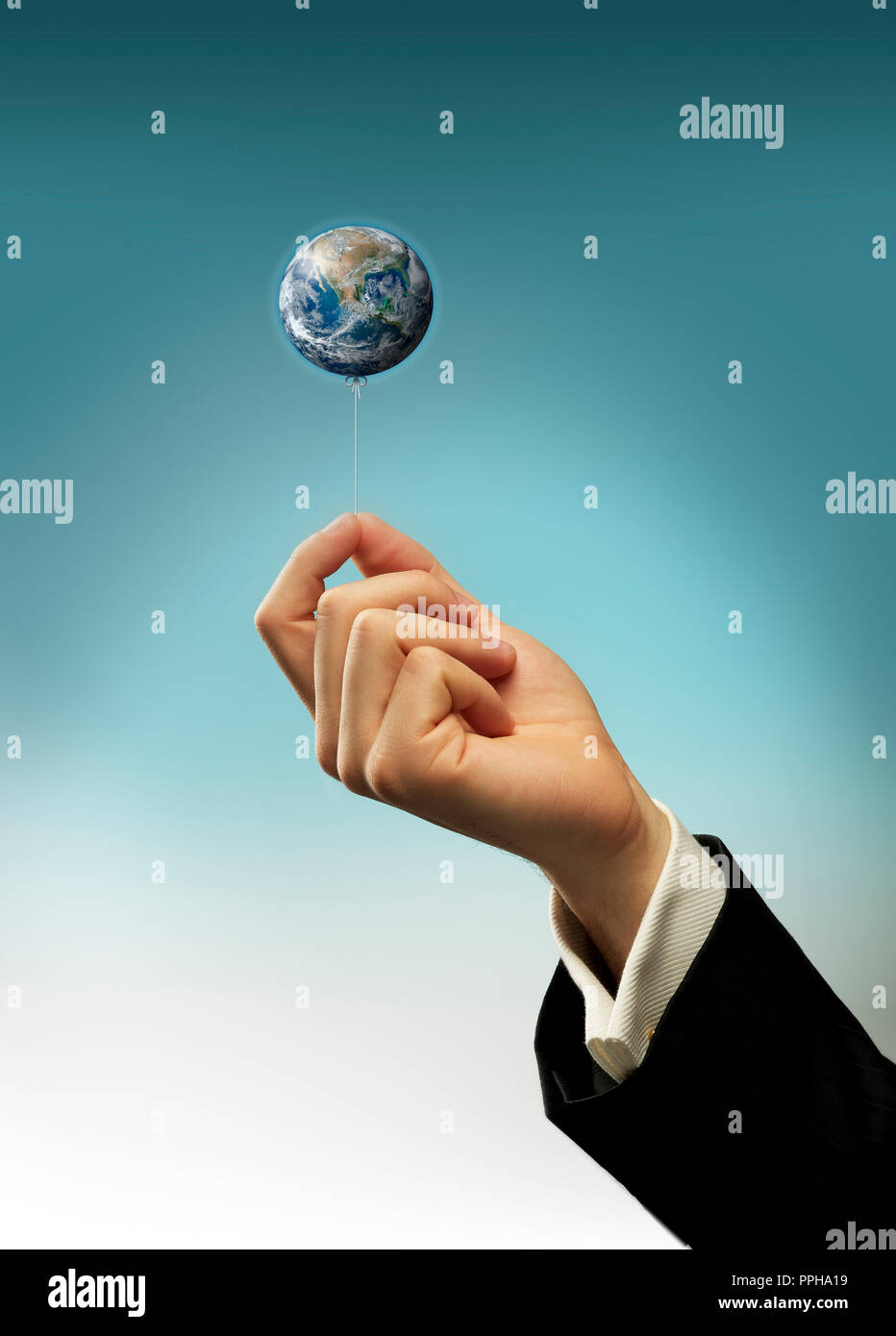 Concept Hand of a business man holding a string of earth balloon - Stock Image