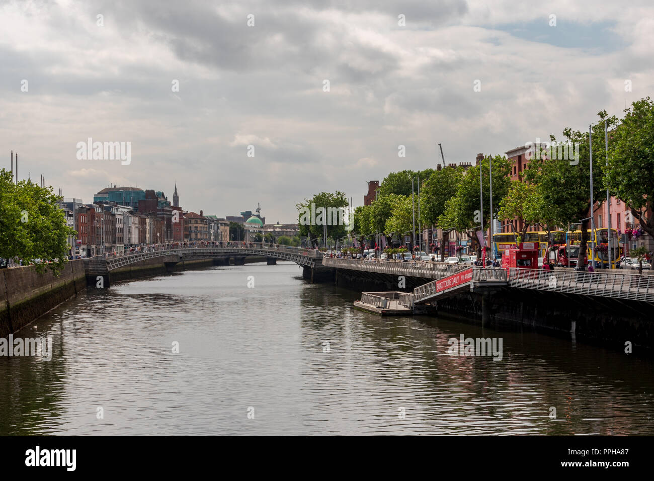 Dublin, Ireland -- July 9, 2018.  The sidewalks and streets of the River Liffey in Dublin Ireland are crowded with travelers and tourists. - Stock Image