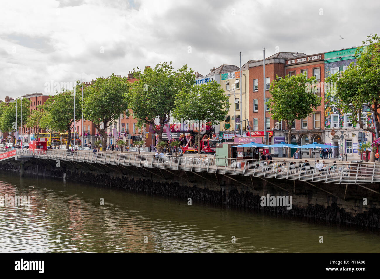 Dublin, Ireland -- July 9, 2018.  Colorful shops line the sidewalks on the banks of the River Liffey in Dublin, Ireland. - Stock Image