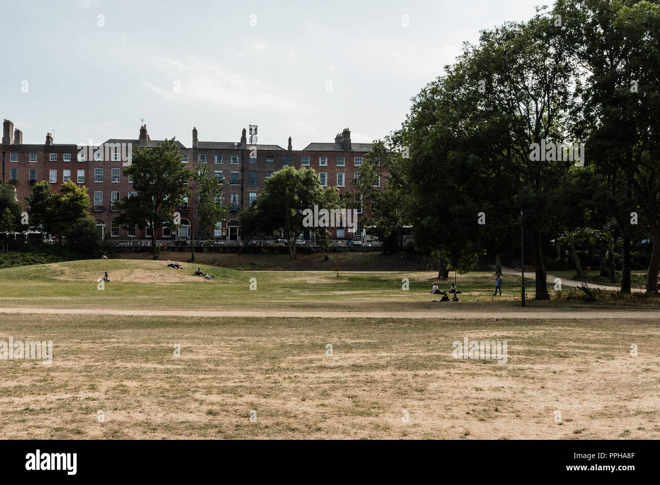 Dublin, Ireland -- July 9, 2018.  Students relax in a Dublin park on a hot summer day. - Stock Image