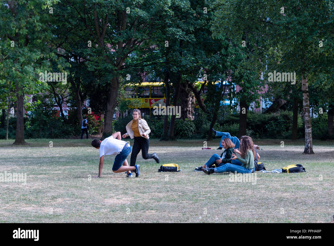 Dublin, Ireland -- July 9, 2018.  Students frolic in a Dublin park on a hot summer day. - Stock Image