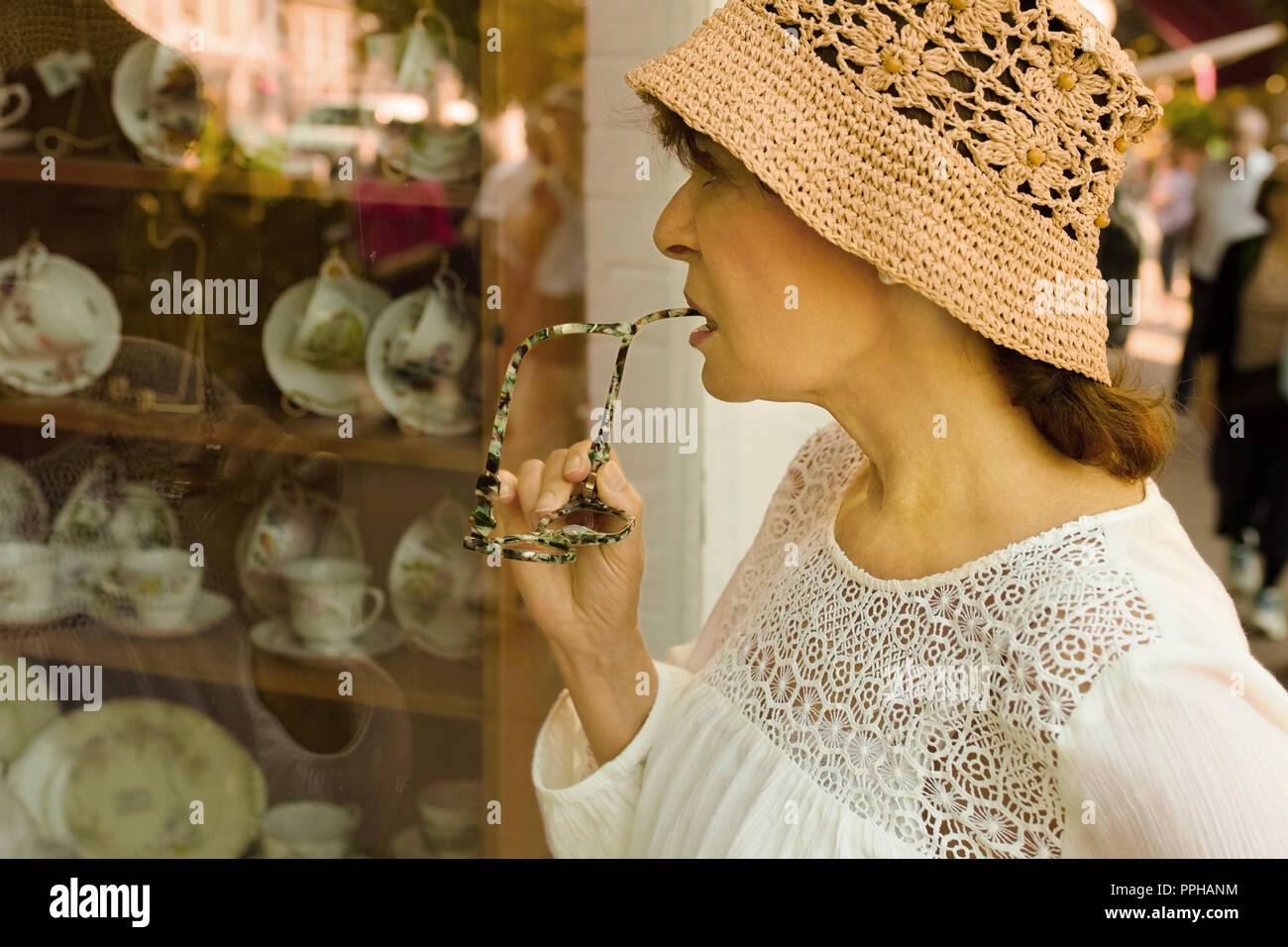 A mature woman gazing at a table decoration shopwindow. - Stock Image