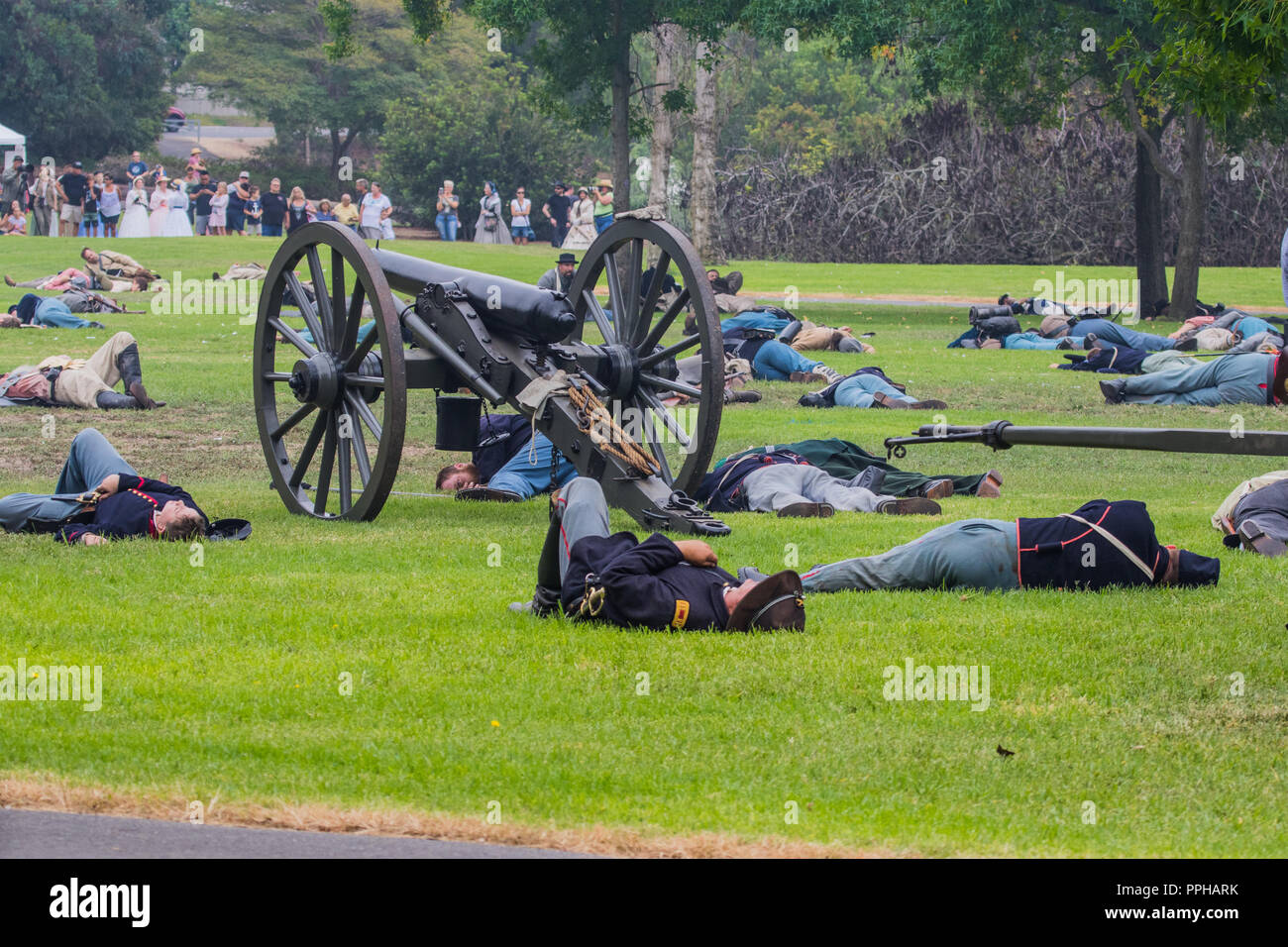 battlefield Casualties laying on the ground  beside a canon during a American Civil war reenactment in Central Park Huntington Beach, California, USA - Stock Image