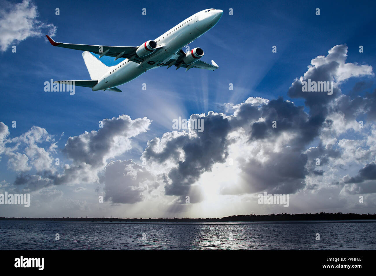 Jet aircraft departing Mascot Airport flying over Botany Bay in a vibrant blue sky, with bright white coloured Sun Rays and cumulonimbus clouds. Sydney - Stock Image