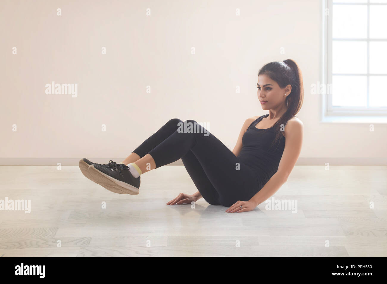 Young woman in workout clothes doing exercises on the floor. - Stock Image