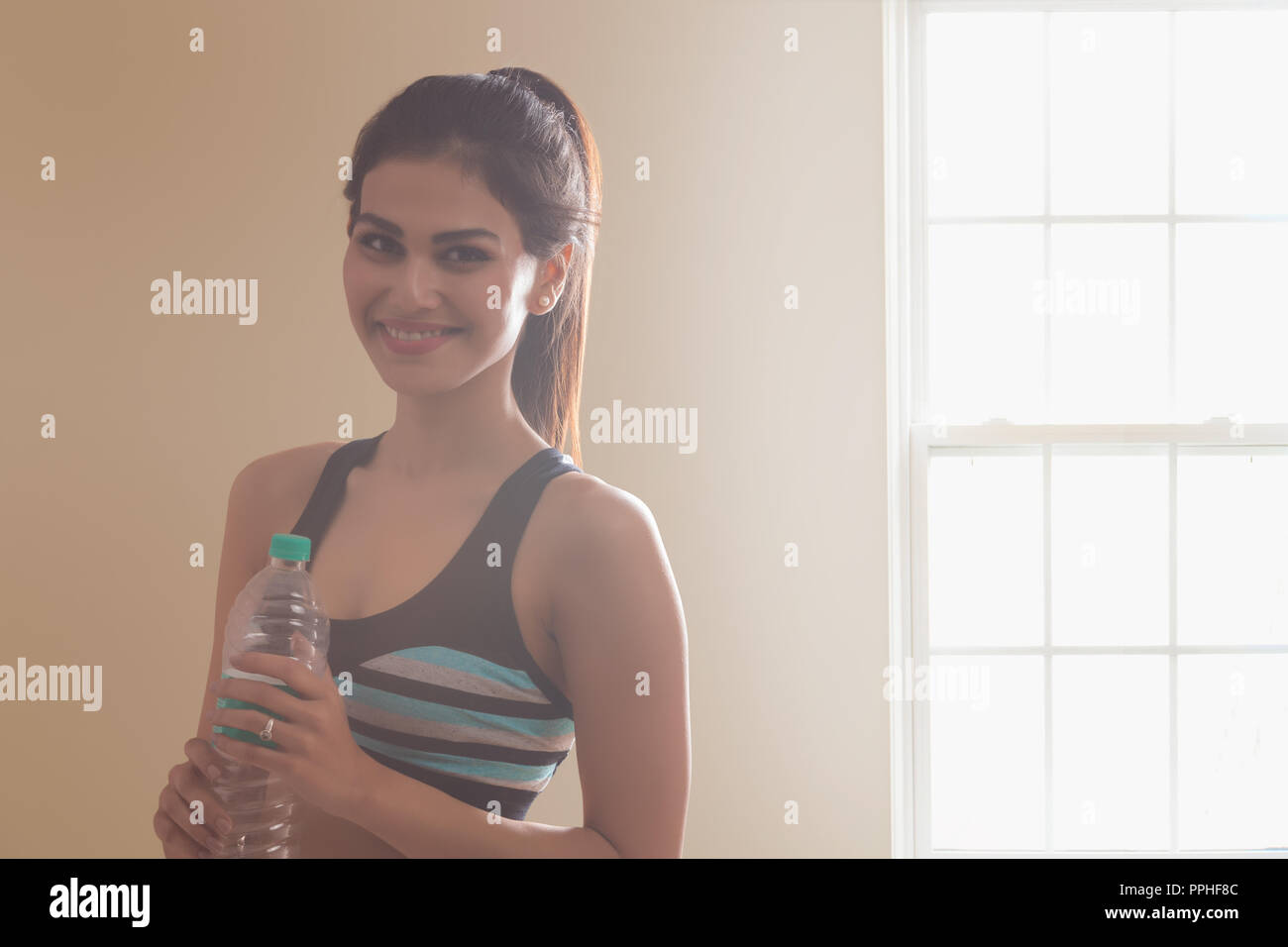 Portrait of a smiling young woman in workout clothes holding water bottle after workout. - Stock Image