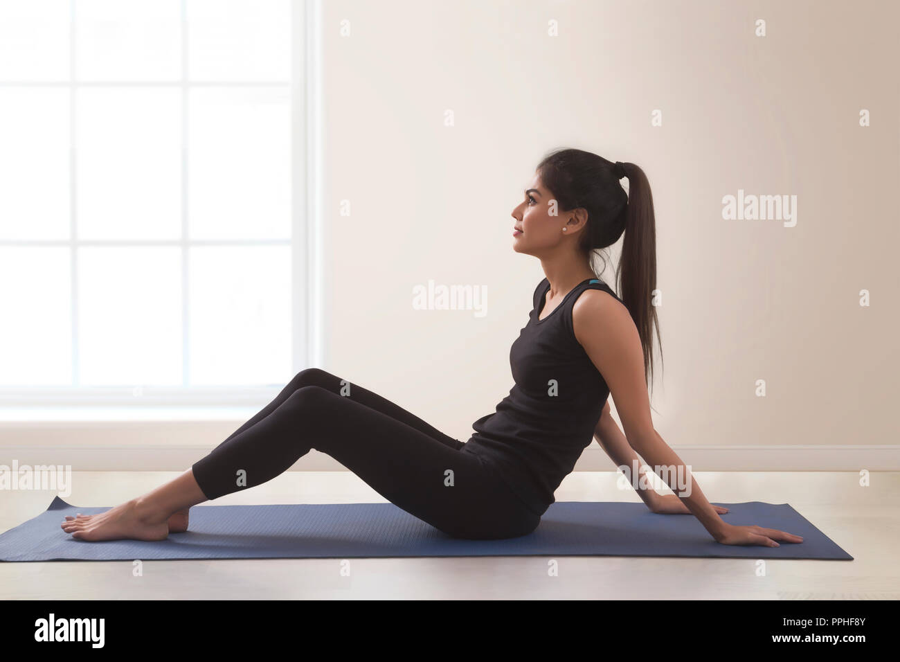 Young fitness woman in workout clothes doing yoga on yoga mat. - Stock Image