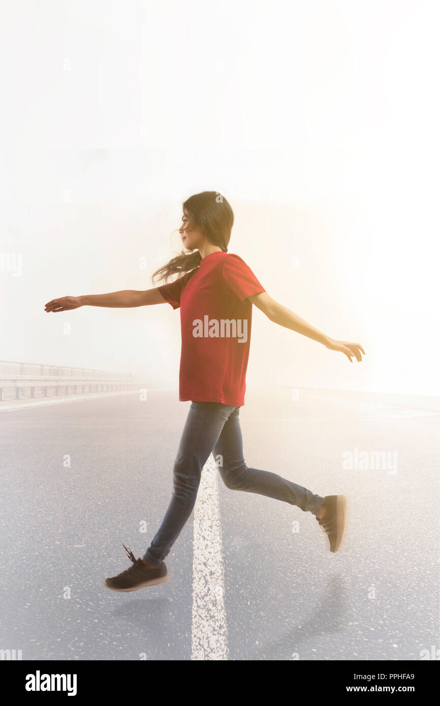 Young woman leaping joyfully in mid air across the road with sun in the background. - Stock Image